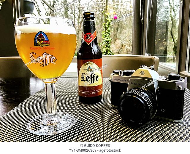 Rotterdam, Netherlands. Analog mirror reflex camera on a cafe's table, neighbored by a glass of beer and a beerbottle during a walkbreak of a photographer