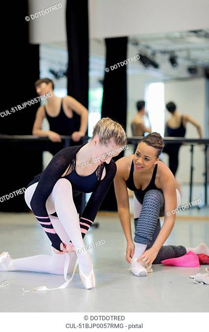 Ballet dancers tying on pointe shoes