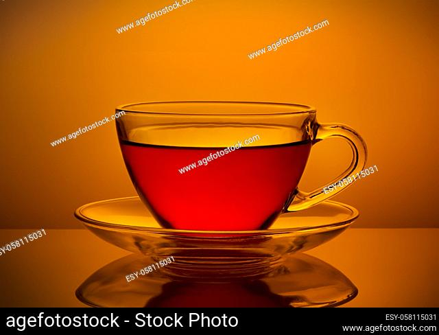 Cup of fresh tea on an orange background