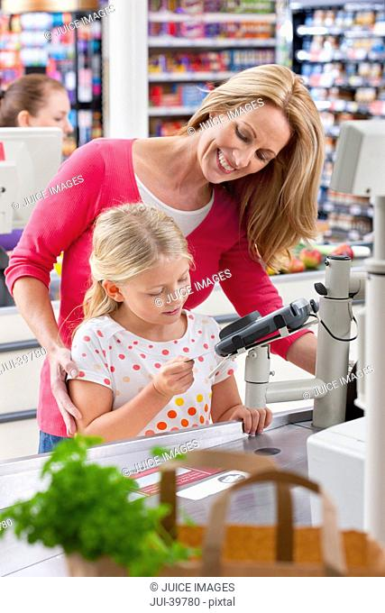 Mother And Daughter Paying For Shopping At Supermarket Checkout