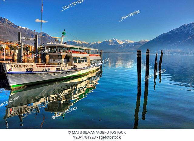 Passenger ship reflected on an alpine lake with snow-capped mountain and blue sky