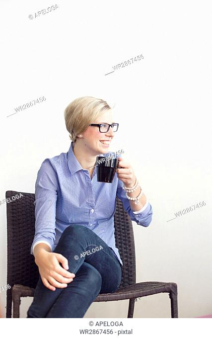 Happy businesswoman holding coffee mug while sitting in creative office