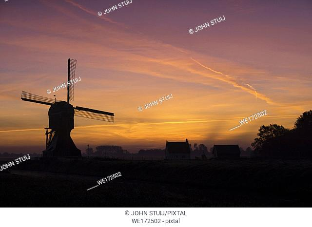 The windmill Laaglandse molen in front of a spectacular sunrise