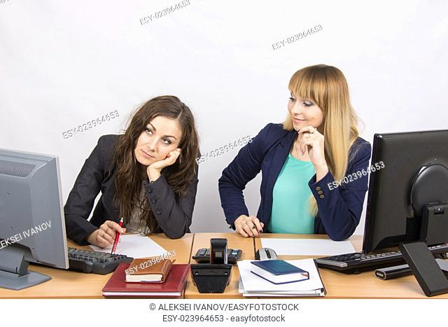 Two young beautiful girls colleagues sitting at the same desk in the office