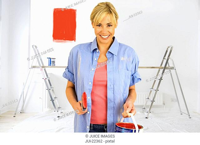 Smiling woman holding paint can with red paint swatch on wall in background