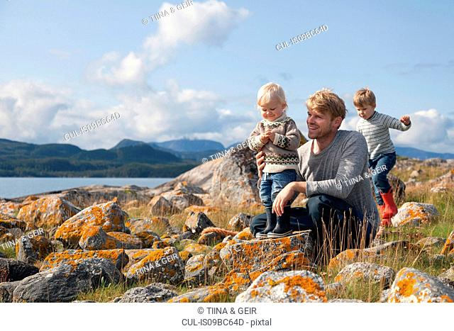 Man with sons playing by fjord, Aure, More og Romsdal, Norway