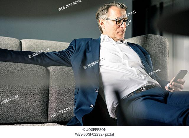 Mature businessman sitting on couch using cell phone