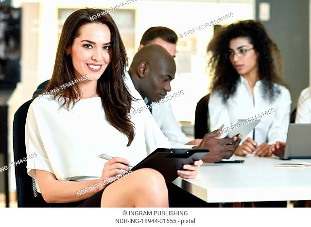 Multi-ethnic group of five businesspeople meeting in a modern office. Caucasian businesswoman leader, wearing white shirt and black skirt, looking at camera