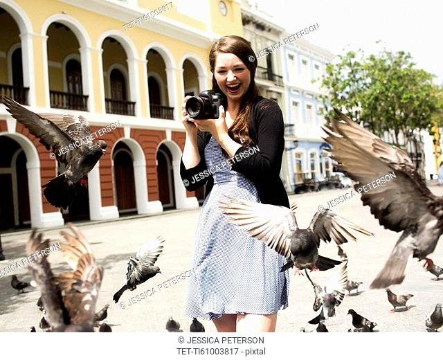 Puerto Rico, San Juan, Woman standing on street and photographing pigeons