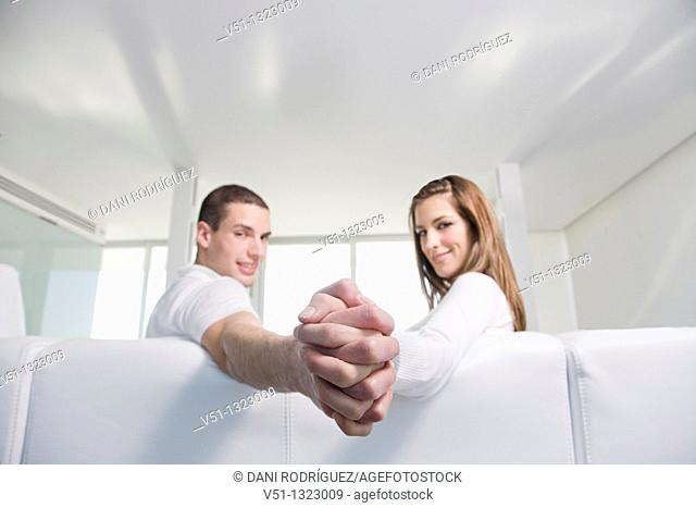 Couple holding hands in sofa