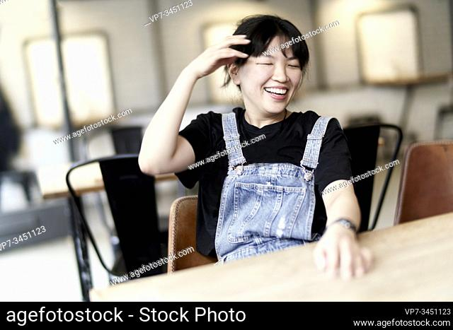 Korean woman sitting at table in cafe, laughing about herself