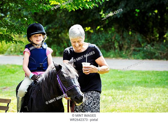 Woman and blond girl wearing riding hat sitting on a pony