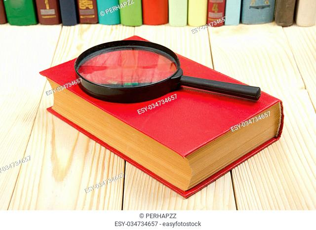 Composition with hardback book and magnifying glass on the table. Back to school, copy space. Education background