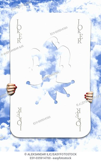 Large Joker Playing Card With Girls Hands Holding It In Sky Background