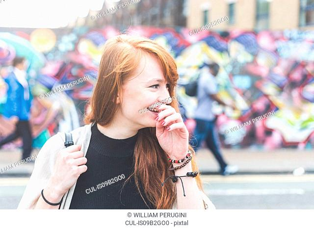 Woman in urban area hand on mouth looking away smiling, London, UK
