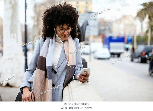 Spain, Barcelona, smiling woman with cell phone and earphones in the city