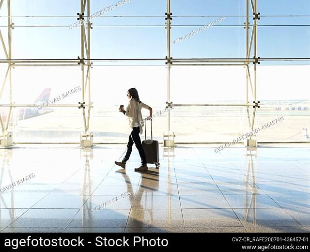 Woman walking with suitcase at the departure hall of the airport