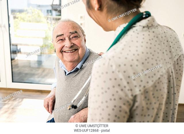 Senior man smiling at nurse at home