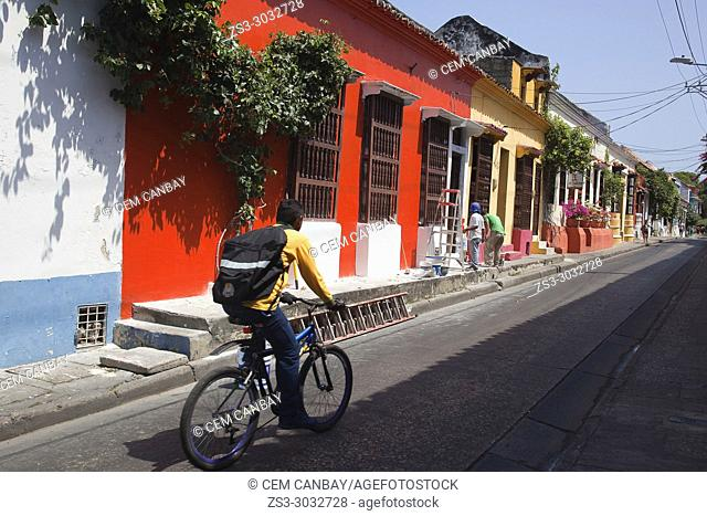 Cyclist in front of the colonial buildings at the historic center, Cartagena de Indias, Bolivar, Colombia, South America