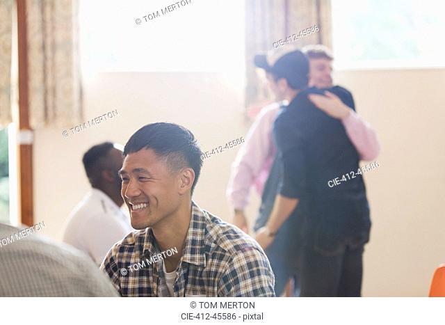 Smiling man enjoying group therapy