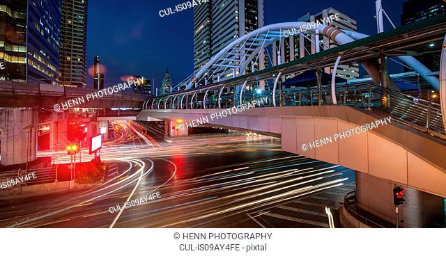 Light trails on road below footbridge, Sathorn, Bangkok, Thailand
