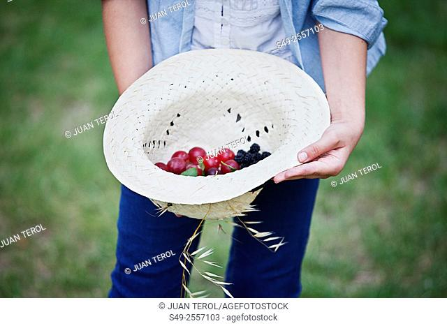 Still life, girl taking a straw hat with berries inside