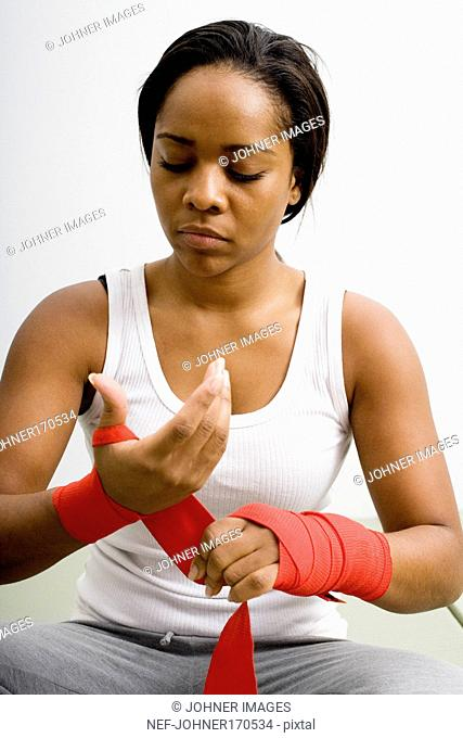 A woman wrapping bandage round her wrists