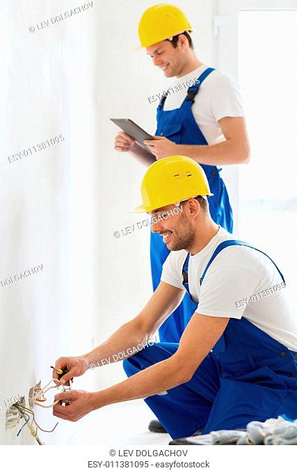 building, renovation, technology, electricity and people concept - two builders with tablet pc computer fixing wiring indoors