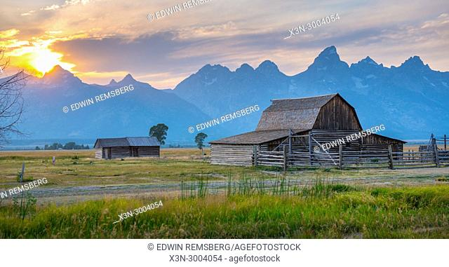Setting sun looms over Teton Mountain Range and historic John Moulton Barn on Mormon Row, Grand Tetons National Park, Teton County, Wyoming. USA