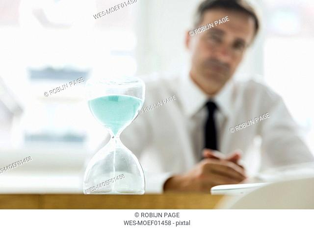 Hourglass on table in office with businessman in background