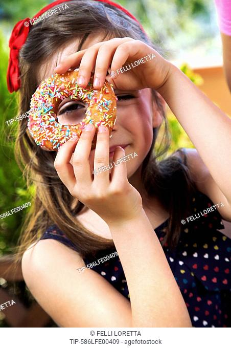 girl with donut during birthday party