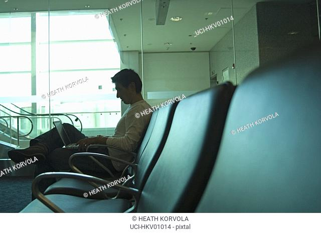Man reading in waiting area of airport