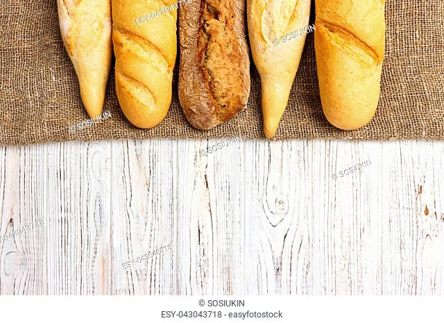 Freshly baked French baguettes on white wooden table. Top view, copy space