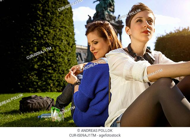 Two young adult women sitting back to back in park