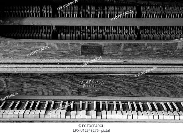 Drinking saloon as seen from inside with detail of piano, desaturated image, Bodie pioneer village, California