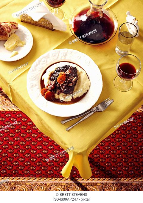 Overhead view of table with beef cheek stew and red wine carafe