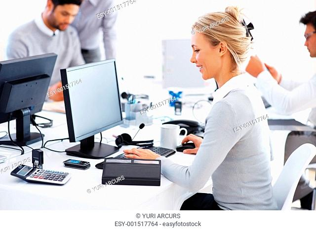 Happy business woman working on computer with colleagues in background