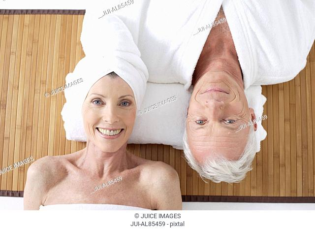 High angle view of senior couple laying on floor smiling