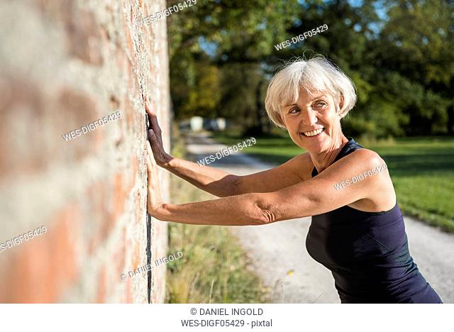 Smiling sportive senior woman leaning against a brick wall