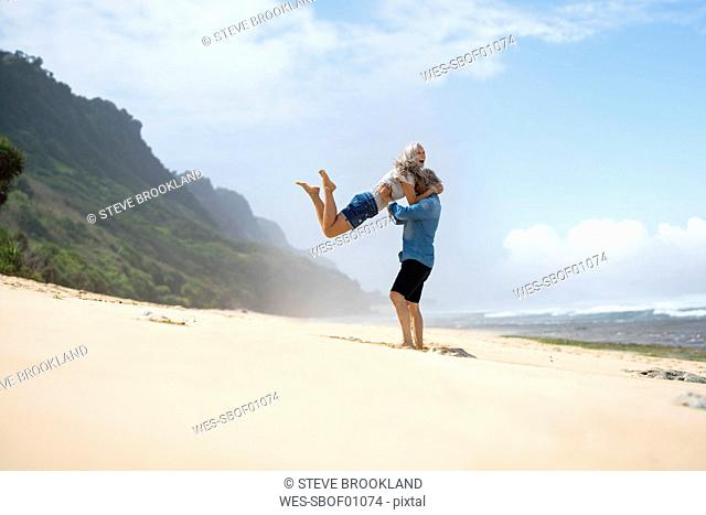 Handsome senior couple having fun on the beach