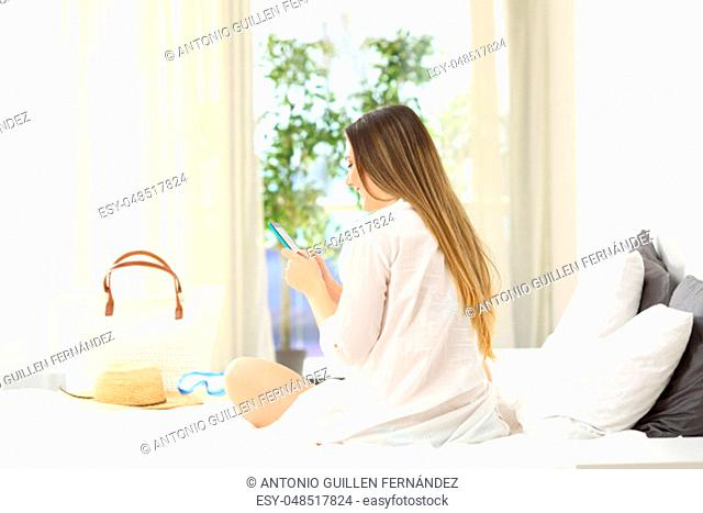 Happy girl using a smart phone sitting on a bed in summer vacations