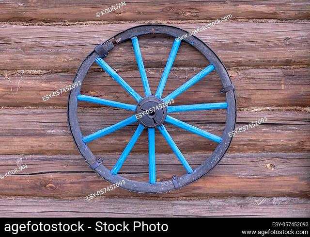 wheels from the cart on the wooden wall of the stables