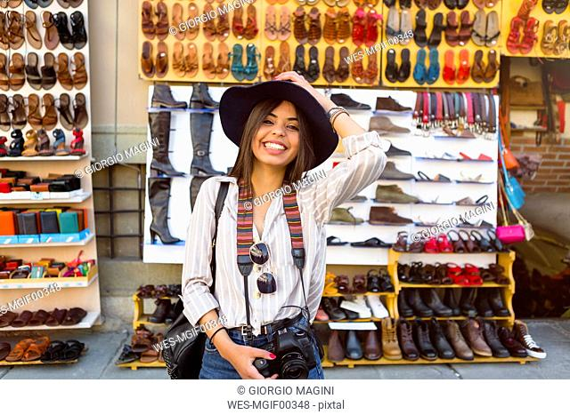 Italy, Florence, portrait of happy young tourist with camera and backpack on street market