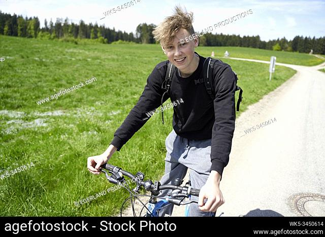 Teenager on bicycle at countryside, in Schaftlach, Bavaria, Germany