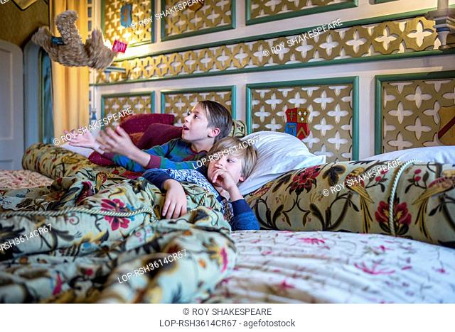 England, Gloucestershire, Thornbury. Two boys in onesies in the biggest hotel bed in Europe at Thornbury Castle