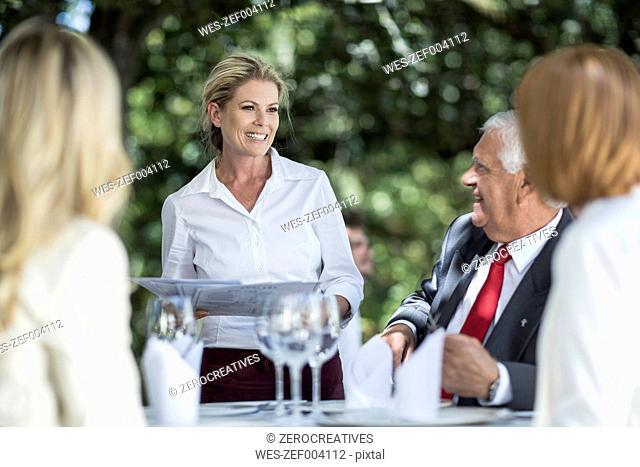 Waitress giving menus to clients at table