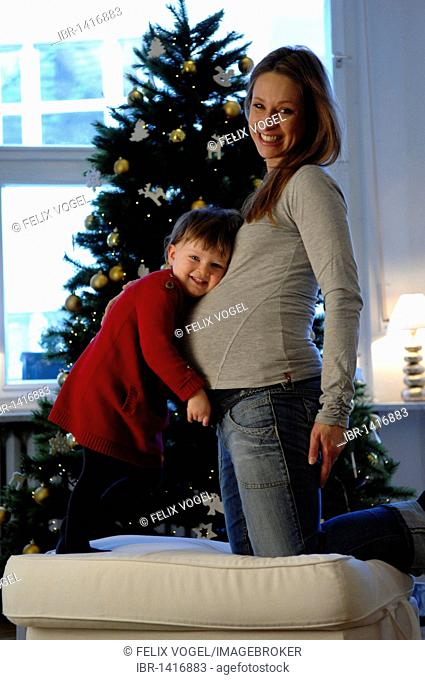 Happy family, daughter and pregnant mother, Christmas tree