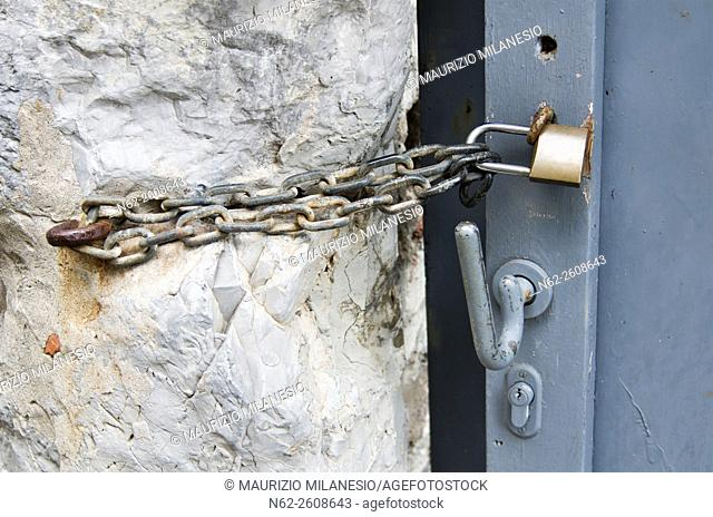 Locked door with padlock and chain attached to a rock wall