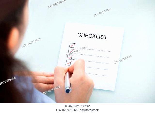 Businesswoman Marking On Checklist