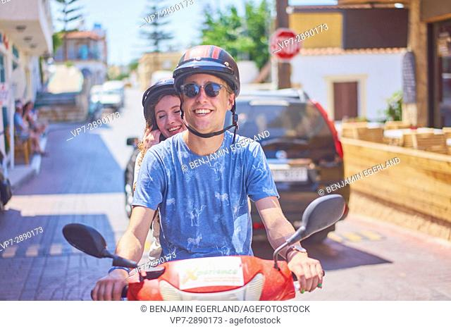 happy young couple enjoying road trip with moped. Hersonissos, Crete, Greece